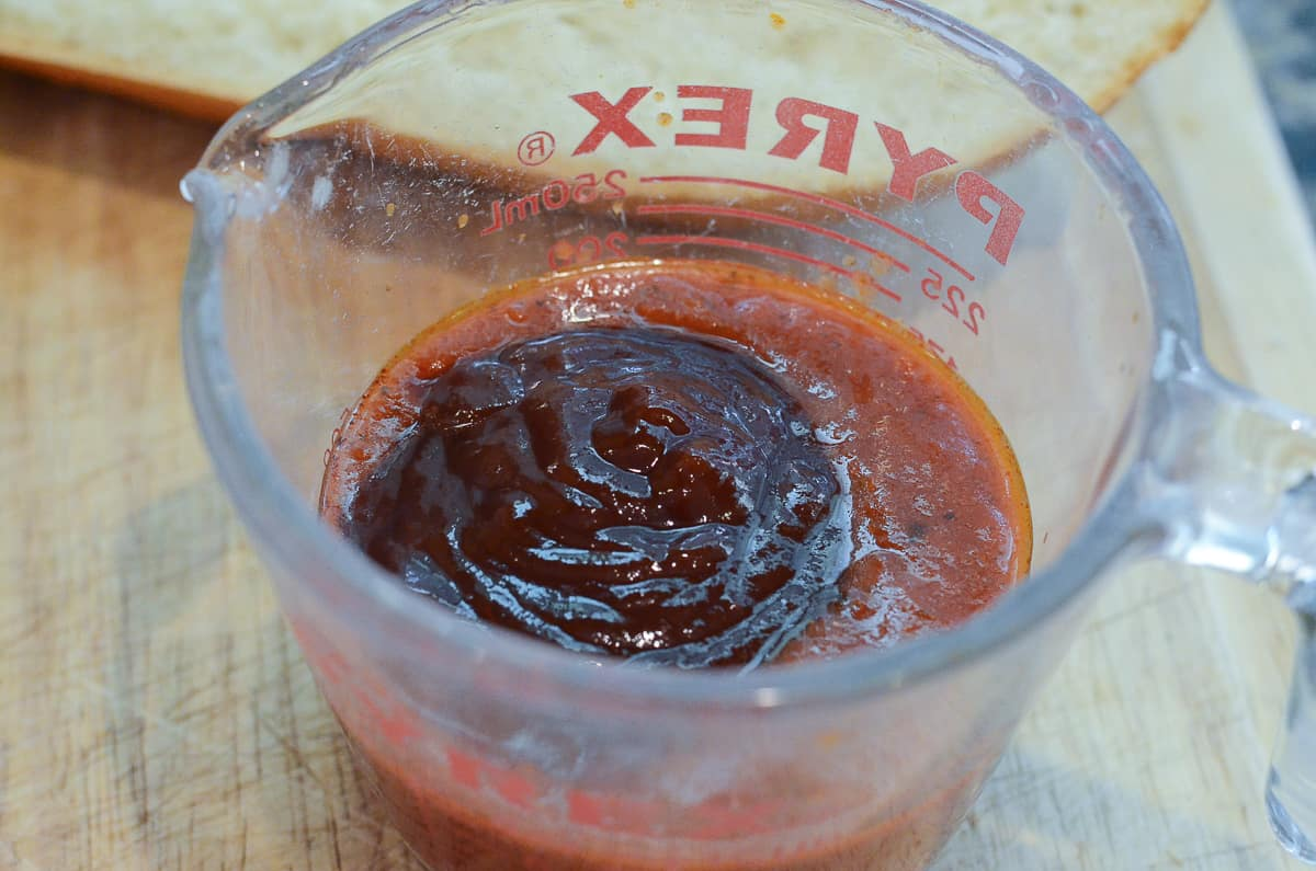Marinara and BBQ sauce in a measuring cup.