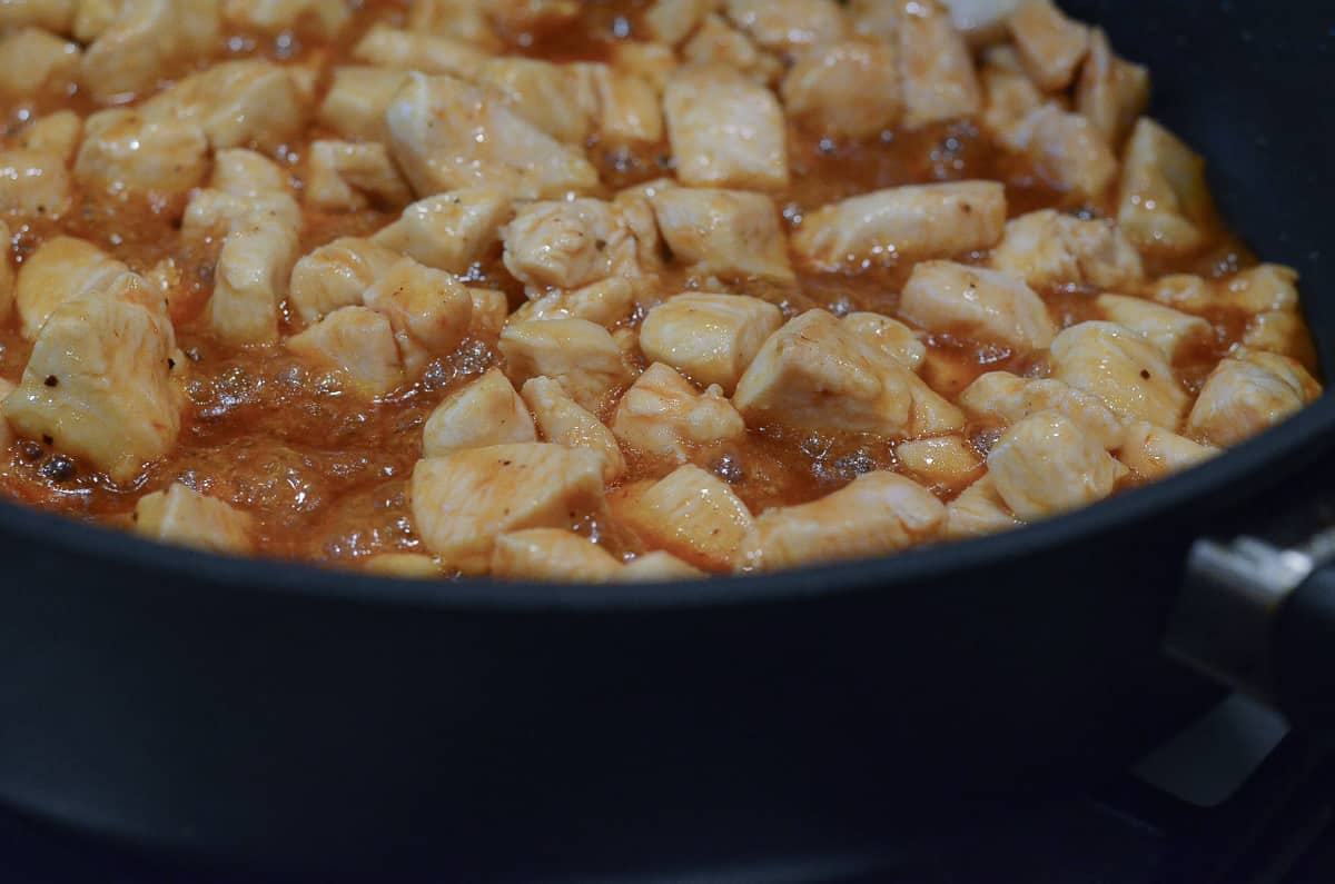 Pieces of chicken simmering in BBQ sauce in a skillet.