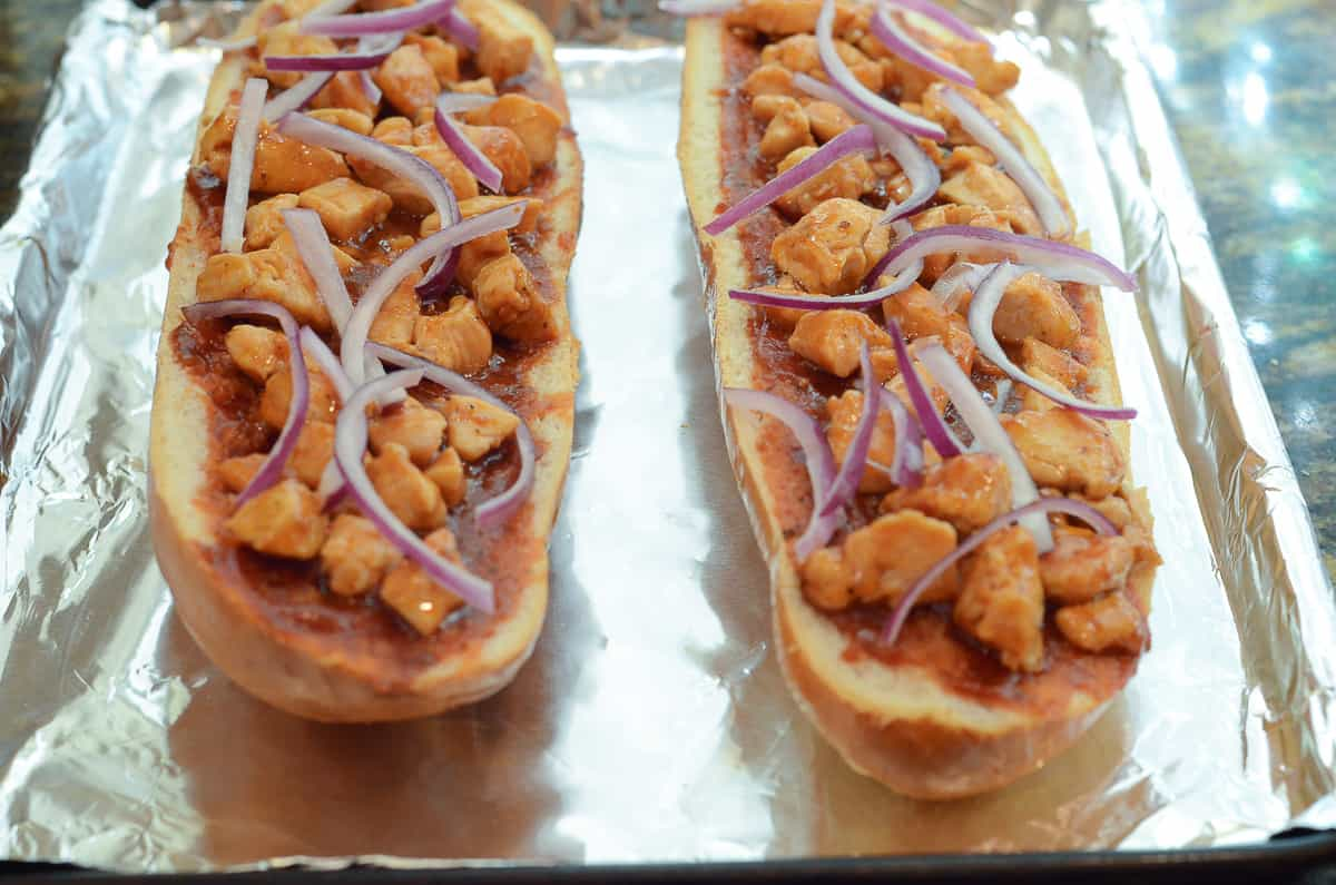 Sliced red onion on top of French bread pizza on a foil lined baking sheet.