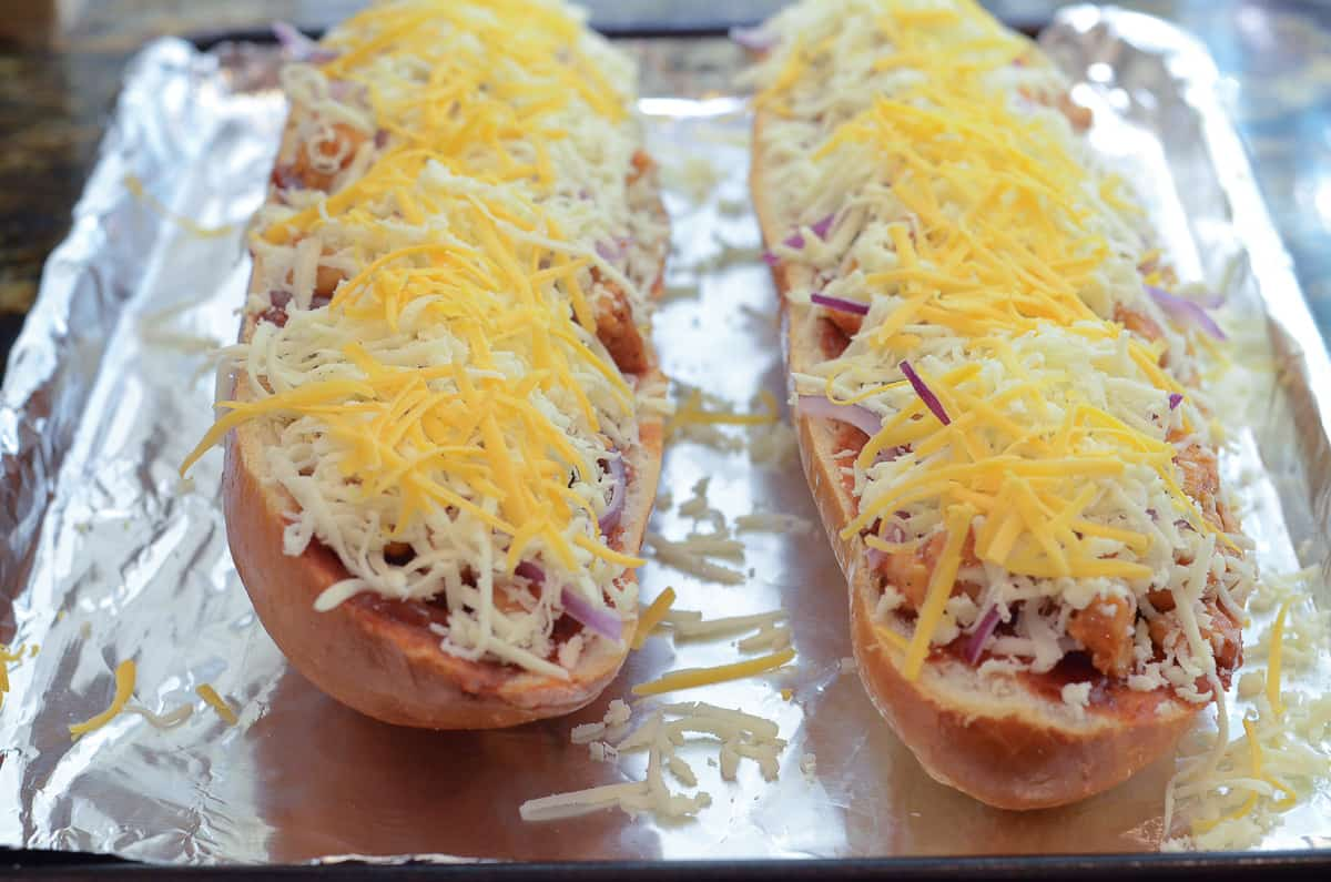 Shredded cheese on top of BBQ Chicken French Bread Pizza on a foil lined baking sheet.