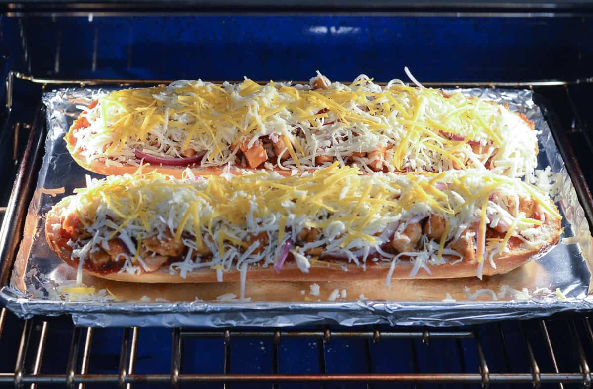 French bread pizza baking in an oven.