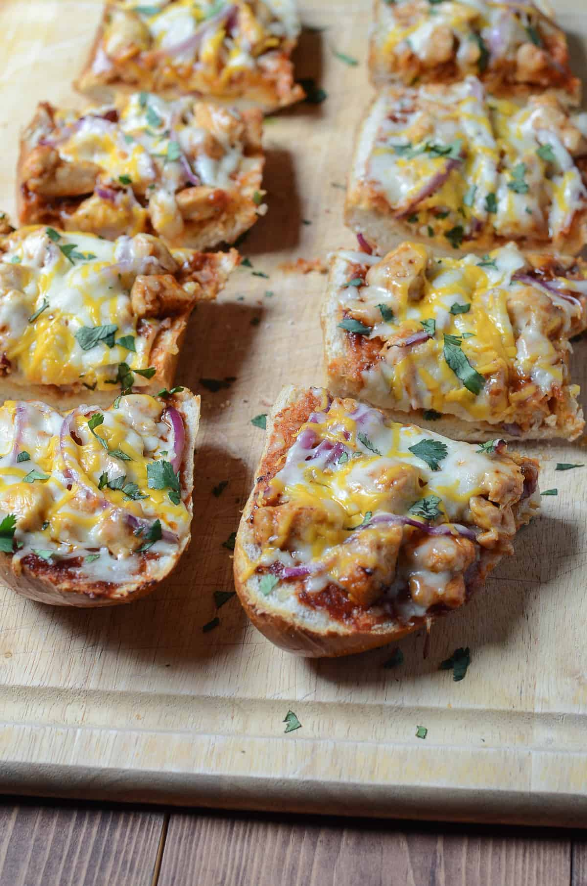Slices of BBQ Chicken French Bread Pizza on a cutting board.