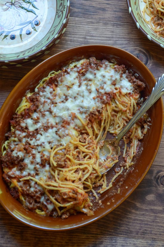 Baked Spaghetti Casserole in a dish with a spoon shot from over the top.