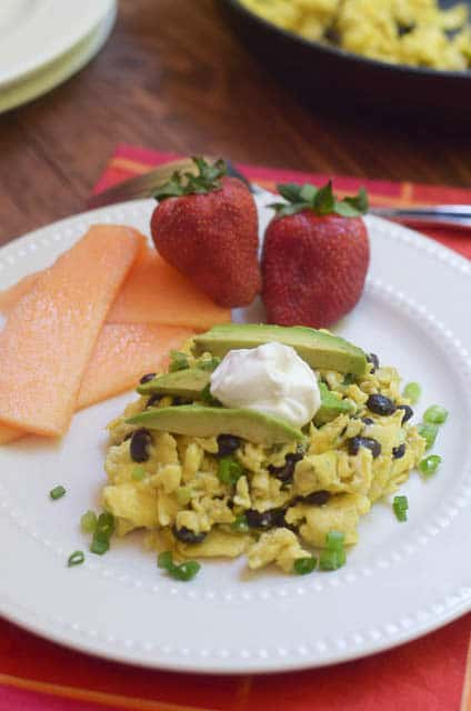 Mexican Scrambled Eggs on a white plate topped with avocado and sour cream with fruit.