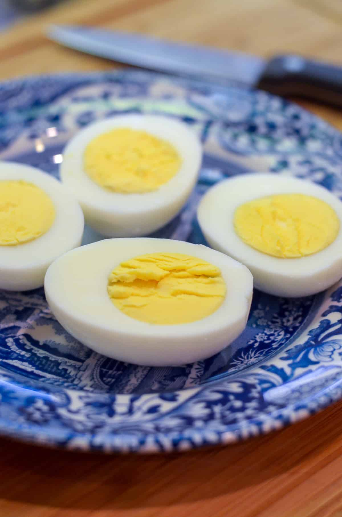 Hard boiled eggs sliced in half on a blue and white plate.