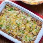 A baking dish full of bean dip with melted cheese.