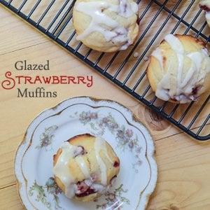 A glazed strawberry muffin on a china plate.