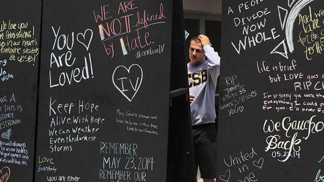 A man standing by blackboards with words on them outside.