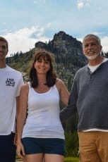 A woman and man standing with a young man in front of a mountain.