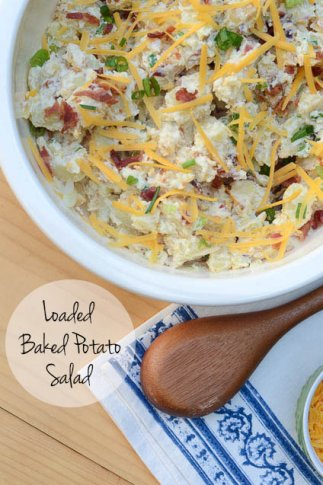 A bowl of potato salad topped with bacon and cheese.