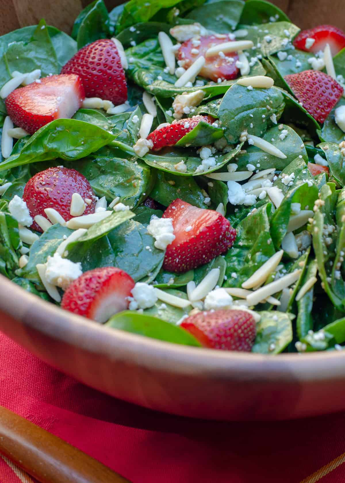 A close up of the Strawberry Spinach Salad in a wooden salad bowl.