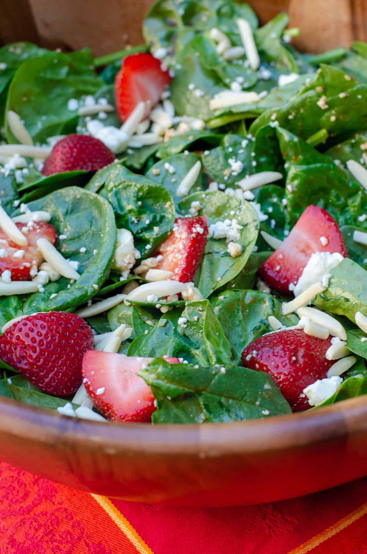 A close up of Strawberry Spinach Salad in a wooden salad bowl on a red cloth.