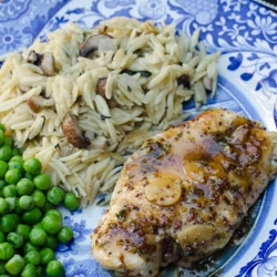Chicken on a plate with rice and peas.
