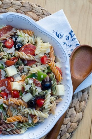 A bowl of pasta salad with olives, cheese, and pepperoni.