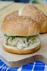 A chicken caesar mixture on a hamburger bun on a cutting board.