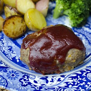 A mini meatloaf topped with sauce on a blue and white plate.