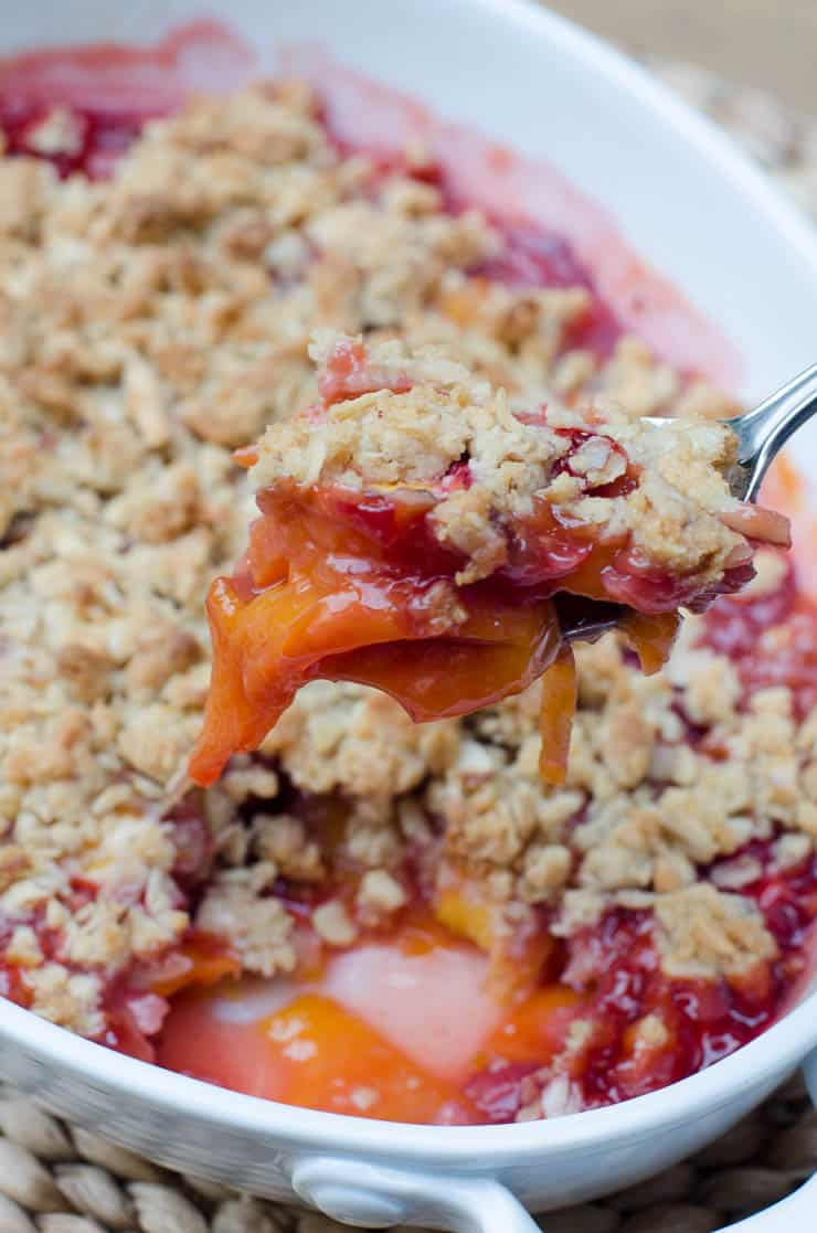 A spoon scoops up some Peach Strawberry Crisp from the baking dish.