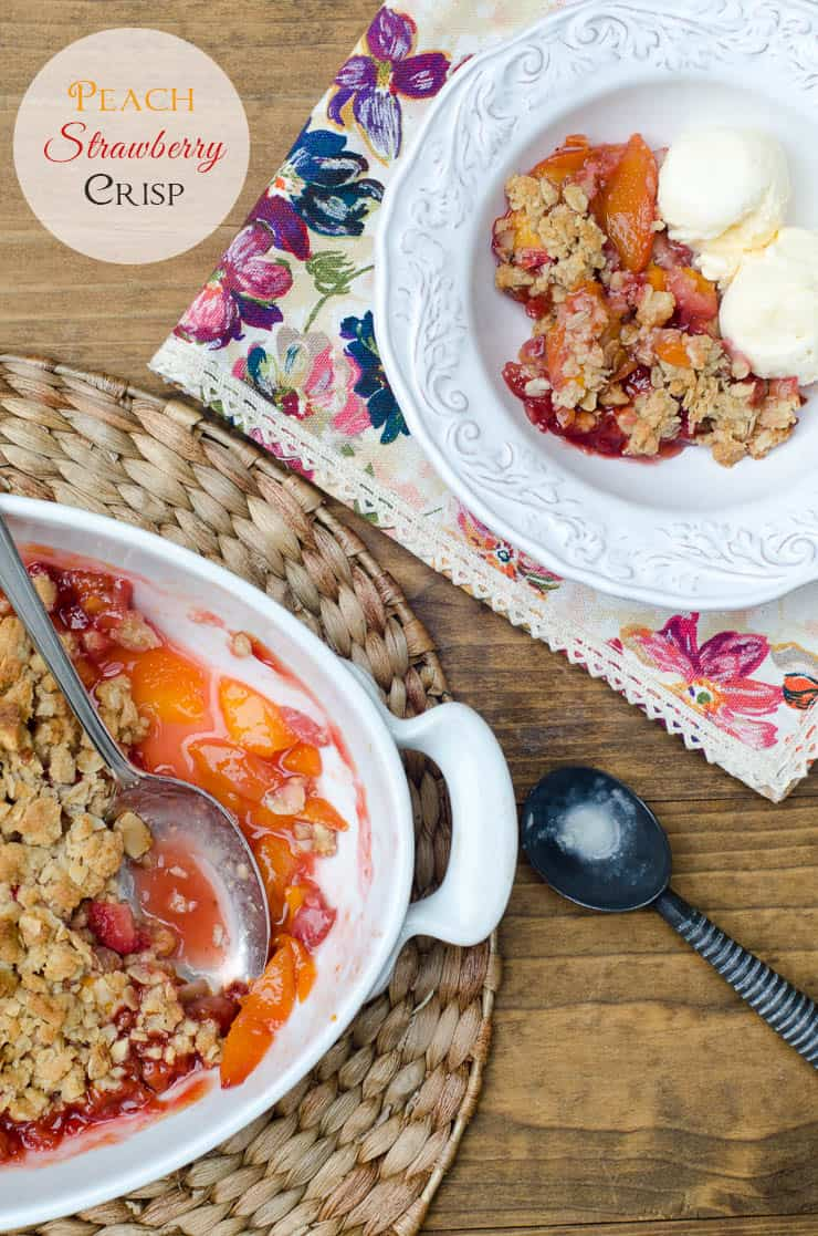 An over the top shot of Peach Strawberry Crisp in a white baking dish and small white bowl with ice cream with text overlay.