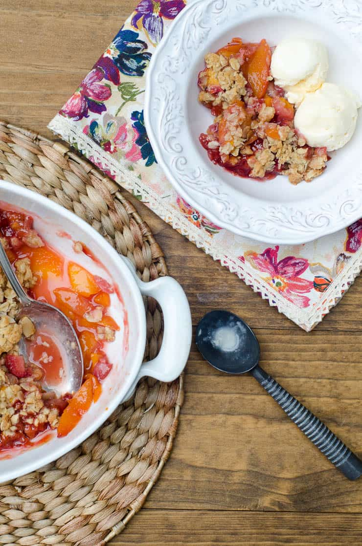 Peach Strawberry Crisp in a white baking dish and small white bowl with ice cream shot from over the top.