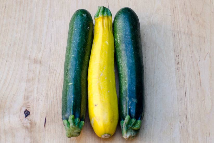 Green and yellow zucchini on a cutting board.