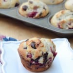 A muffin with raspberries and dark chocolate chips on a white plate.