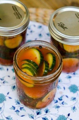A mason jar filled with pickles in a reddish brine.