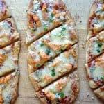 Flatbread pizza on a cutting board.