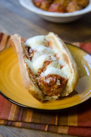 A meatball sandwich on a yellow plate.