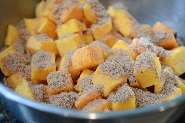 Cubed butternut squash coated with spices in a bowl.