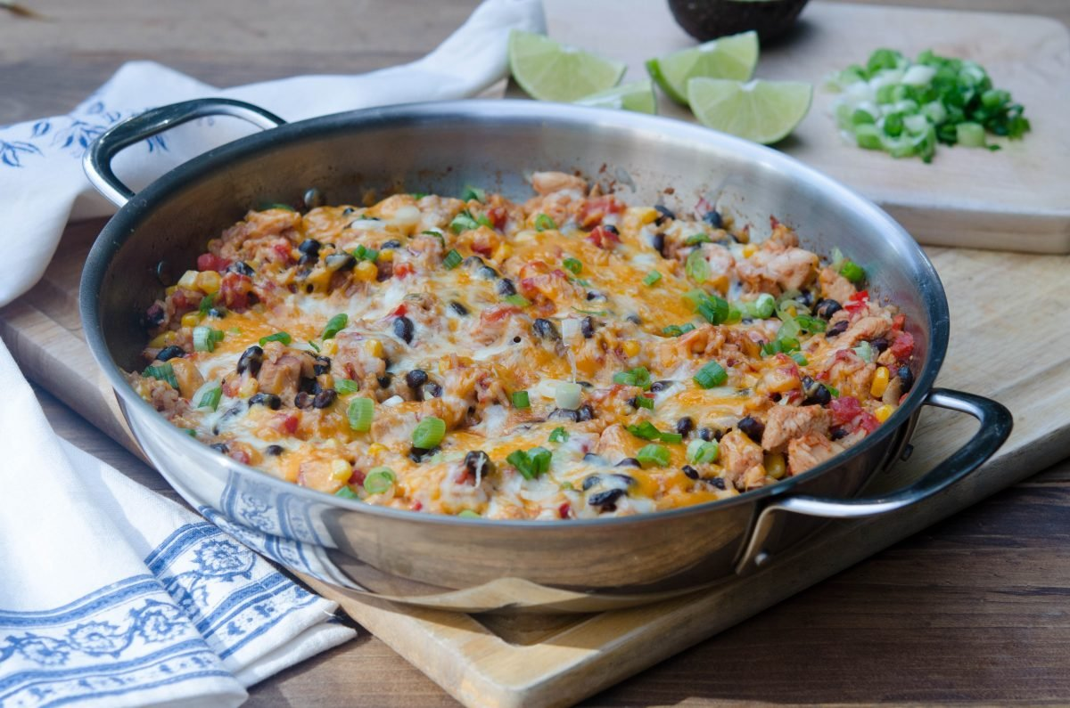 One Pot Tex-Mex Chicken and Rice in a stainless steel skillet with cut limes in the background
