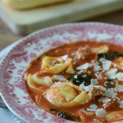 A red and white bowl filled with sausage and tortellini soup with kale.