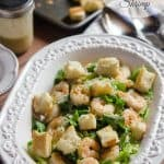 Caesar salad with shrimp and croutons in a white bowl.