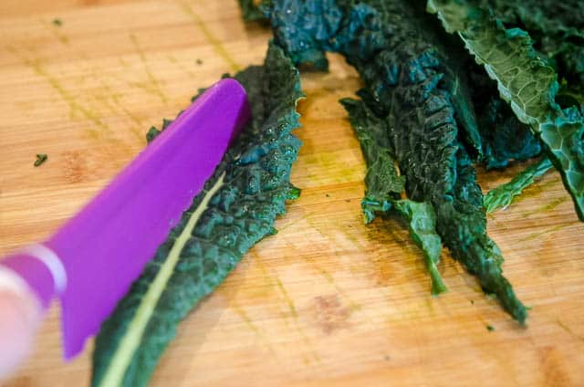 De-stemming kale with e purple knife.