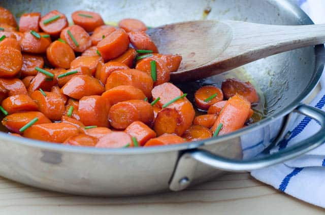 Bourbon Glazed Carrots in a skillet with a wooden spoon.
