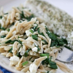 Orzo with spinach and feta on a white plate.