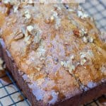 A loaf of banana bread with glaze and nuts.