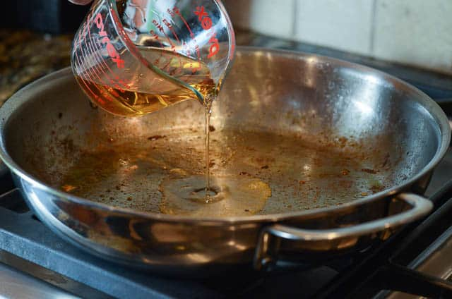 Bourbon pours from a measuring cup into a skillet.