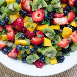A white bowl filled with fruit salad.