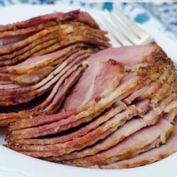 Slices of glazed ham on a white platter.