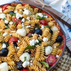 A bowl filled with pasta salad with tomatoes, olives, and cheese.