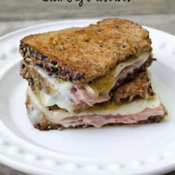 A grilled cheese sandwich with ham sliced in half and stacked on a white plate.