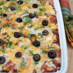 A casserole dish filled with baked chicken enchilada casserole.