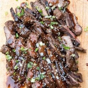 Sliced teriyaki steak topped with sesame seeds on a cutting board.