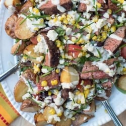 Steak salad with roasted potatoes on a white platter.