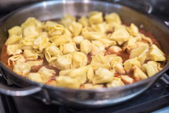 Cheese tortellini is added to the skillet.