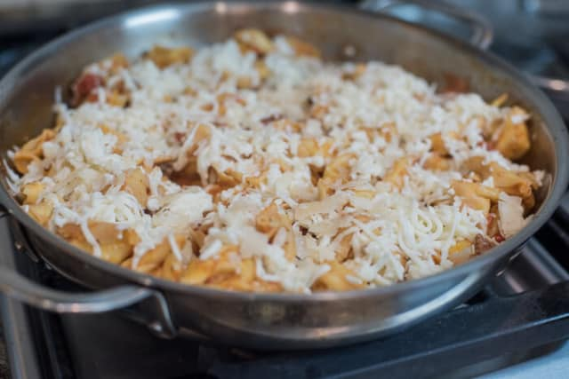 Cheese is sprinkled over the top of the mixture in the skillet.