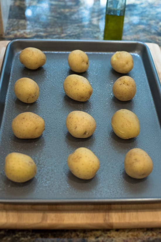 Yellow potatoes lined up on a greased baking sheet.