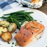 Salmon, potatoes and green beans on a white plate.