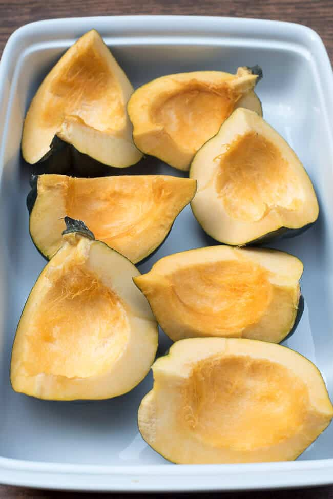 Pieces of acorn squash in a white baking dish.