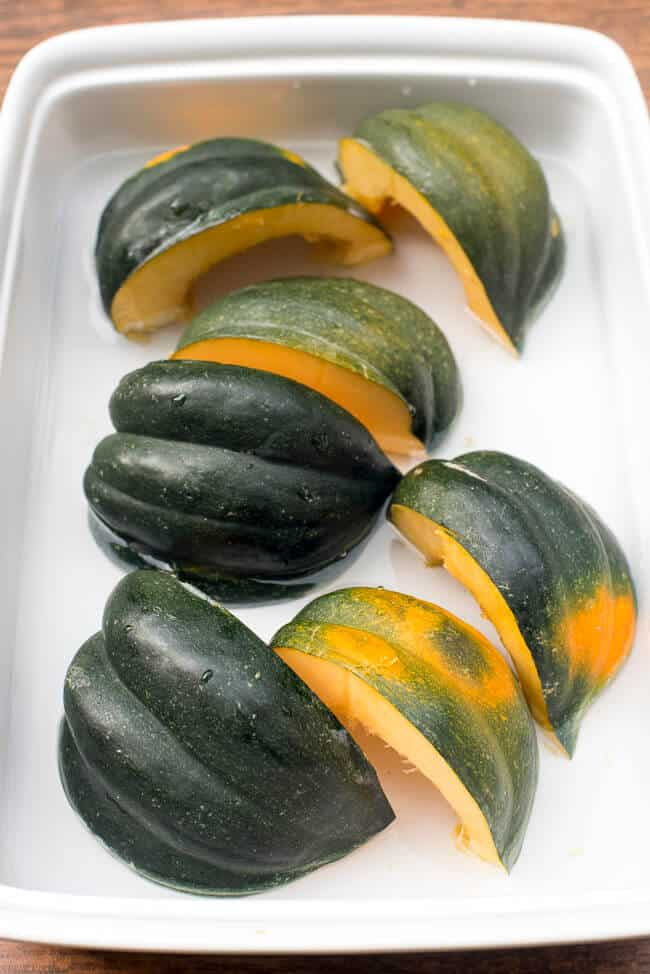 Acorn Squash with the skin side up in a baking dish with a little water.